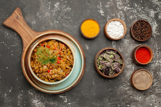 그릇에 있는 향신료 옆에 있는 나무 판자에 토마토를 넣은 녹색 콩 접시