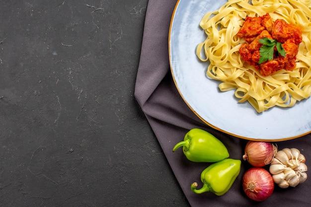 보라색 식탁보에 있는 양파 녹색 볼 후추 옆에 고기와 허브를 곁들인 식욕을 돋우는 파스타의 상단 클로즈업 보기