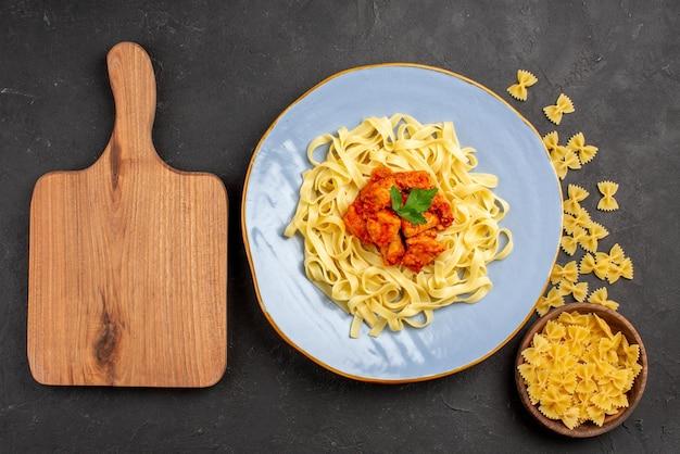 Сверху крупным планом тарелка с макаронами синяя тарелка с аппетитной пастой, соусом и мясом рядом с миской с макаронами и разделочной доской на темном столе