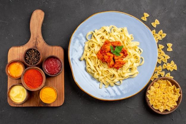 Сверху крупным планом тарелка с макаронами синяя тарелка с аппетитной пастой с подливкой и мясом рядом с миской с макаронами, специями и соусами на разделочной доске на темном столе