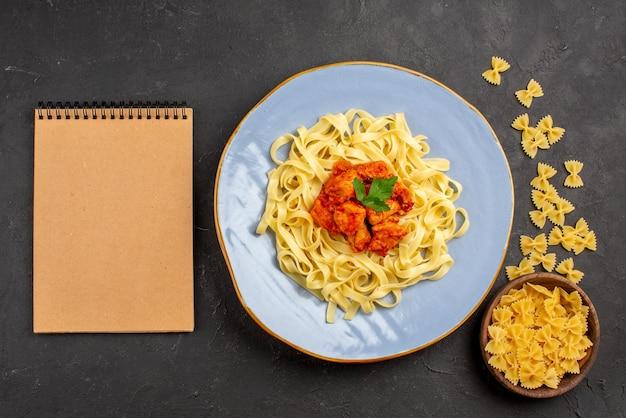 Тарелка с макаронами сверху крупным планом синяя тарелка с аппетитной пастой с подливкой и мясом рядом с блокнотом с кремом и миской макарон на темном столе