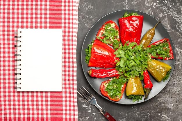 唐辛子の上部のクローズアップビュープレート唐辛子のフォークプレートテーブルクロス上の白いノート