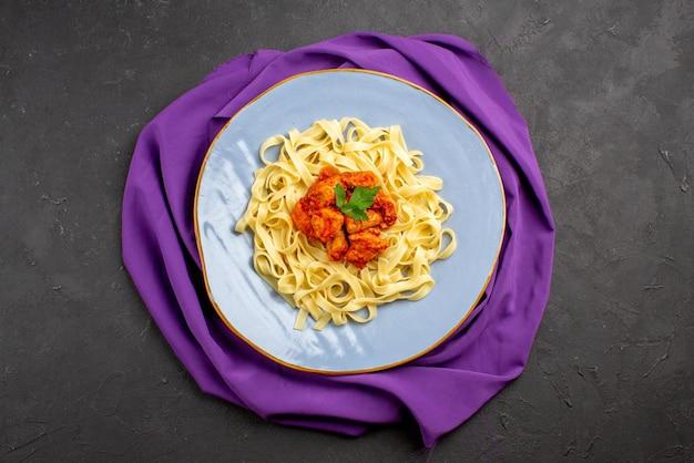 Верхняя тарелка крупным планом на скатерти, соус, мясо и макароны на фиолетовой скатерти на темной поверхности