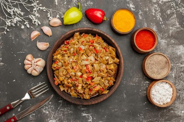 カラフルなスパイスのテーブルボウルの上のクローズアップビュープレートトマトニンニクボールペッパー暗いテーブルのフォークとナイフの横にあるサヤインゲンの食欲をそそる料理