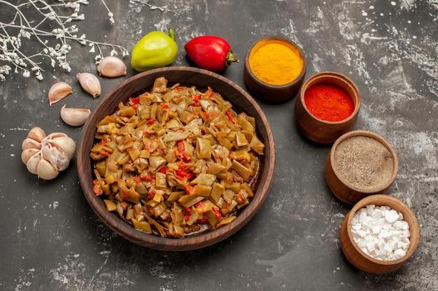 Piatto vista ravvicinata dall'alto sul tavolo ciotole di spezie aglio peperone accanto al piatto appetitoso di fagiolini sul tavolo scuro