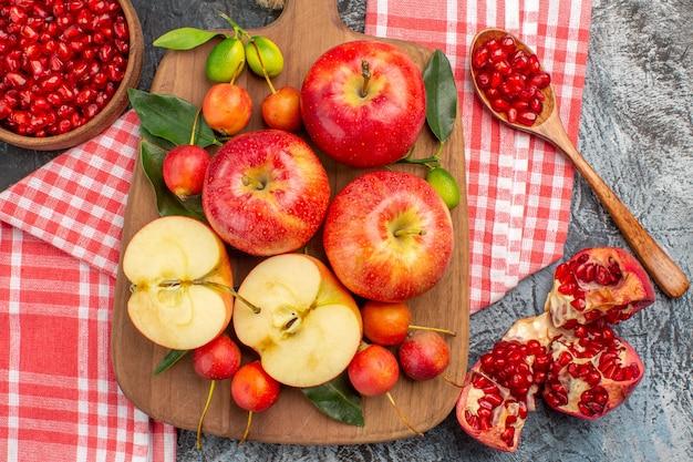 上のクローズアップビューザクロのテーブルクロスボウルのボード上のザクロリンゴチェリー