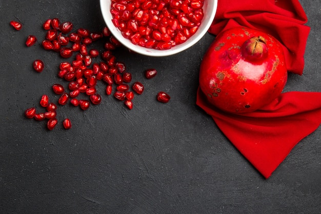 Top close-up view pomegranate bowl with seeds of pomegranate red tablecloth pomegranate