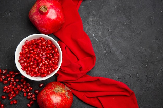 Top close-up view pomegranate red ripe pomegranates pomegranate seeds in the bowl red tablecloth