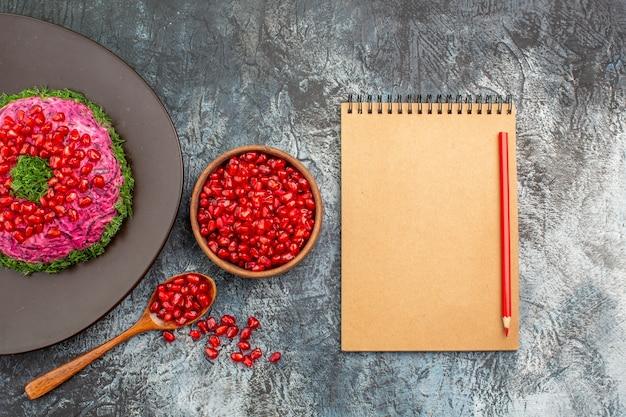 Top vista ravvicinata melograni una ciotola piatto appetitoso di matita taccuino semi di melograno