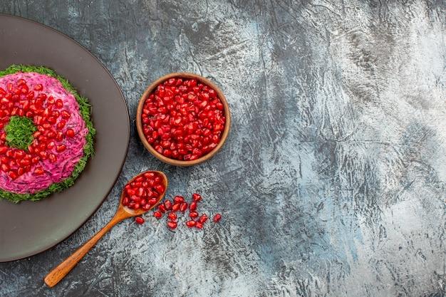 Top vista ravvicinata melograni un piatto appetitoso e una ciotola di semi di melograno