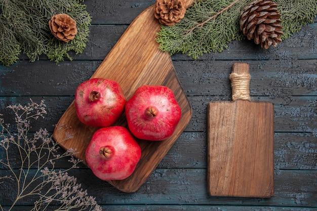 Vista ravvicinata dall'alto melograni e melograni da tavola sul tagliere della cucina accanto al tagliere e rami di abete rosso con coni
