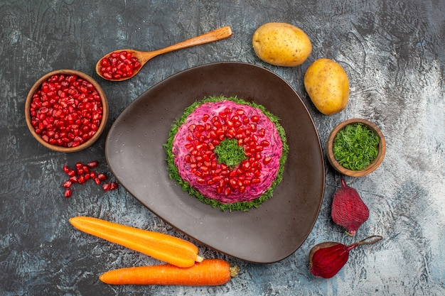 Top close-up view pomegranates dish bowl of pomegranate seeds herbs vegetables