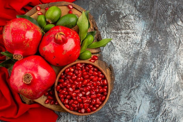Top close-up view pomegranates pomegranate and pomegranate seeds on the board on the red tablecloth