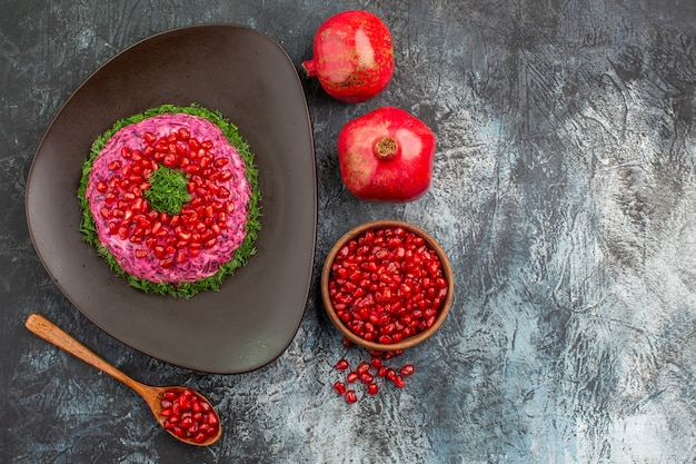 Top close-up view pomegranates pomegranate seeds spoon an appetizing dish with pomegranate herbs