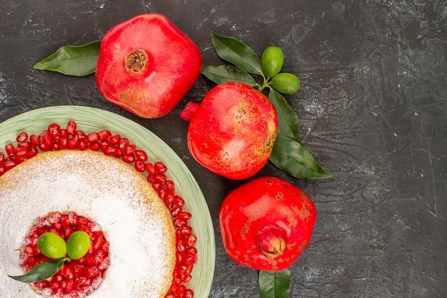상위 클로즈업 보기 석류 잎이 있는 석류 세 개와 석류 씨앗이 있는 케이크