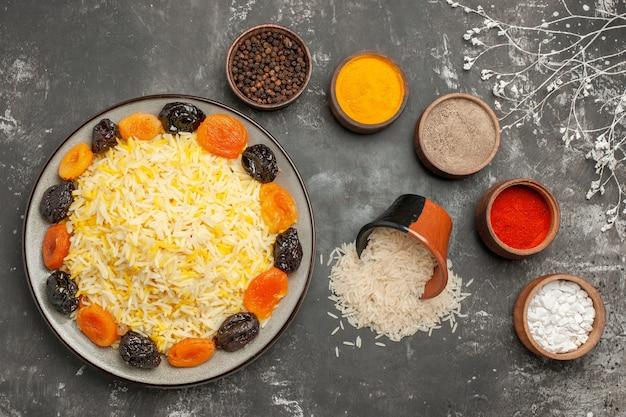 쌀의 말린 과일 그릇과 쌀의 다채로운 향신료 접시의 상위 클로즈업보기 밥 그릇