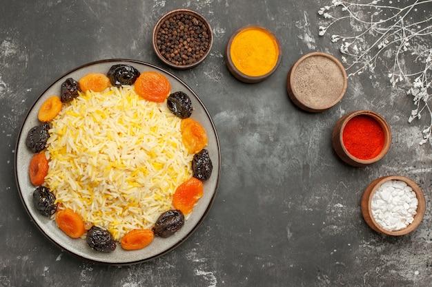 Верхний вид крупным планом рисовые миски с красочными специями, тарелка риса с сухофруктами ветвями деревьев