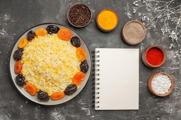 말린 과일 흰색 노트북과 쌀의 다채로운 향신료 접시의 상위 클로즈업보기 밥 그릇