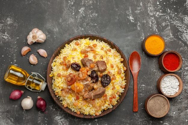 Вид сверху крупным планом рисовый лук, чеснок, бутылка масла, ложка, аппетитные специи для плова