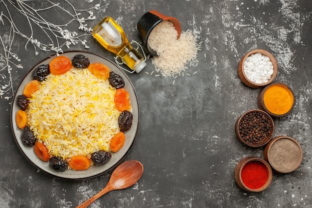 Vista ravvicinata dall'alto cucchiaio di riso bottiglia di olio piatto di riso con frutta secca ciotole di spezie e riso