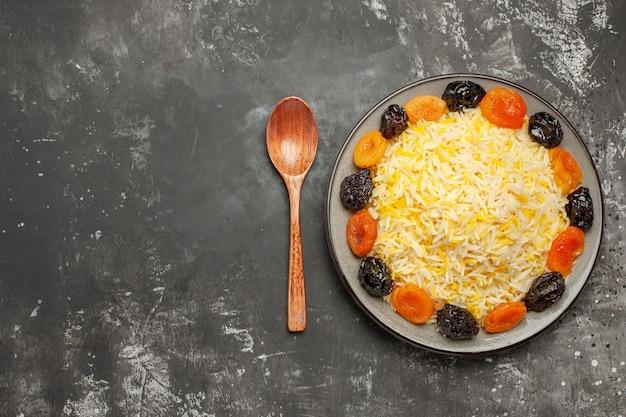 테이블에 접시에 말린 과일과 상위 확대보기 쌀 나무 숟가락 쌀