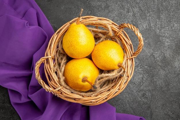 Vista ravvicinata dall'alto pere mature nel cesto tre pere mature nel cesto di legno sulla tovaglia viola sul tavolo scuro