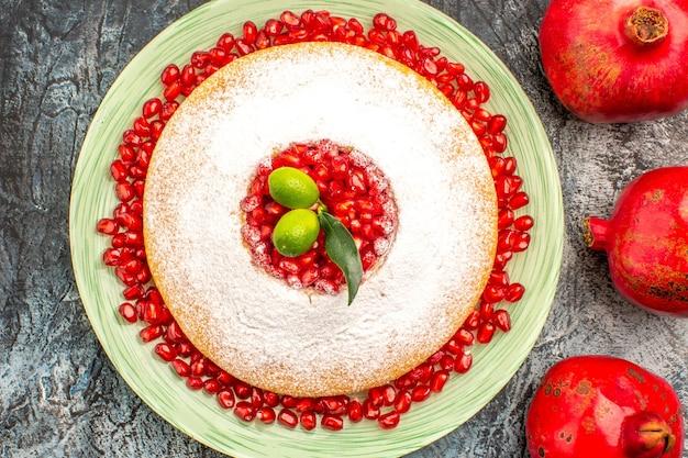 Vista ravvicinata dall'alto melograni maturi melograni rossi accanto al piatto di torta con melograno