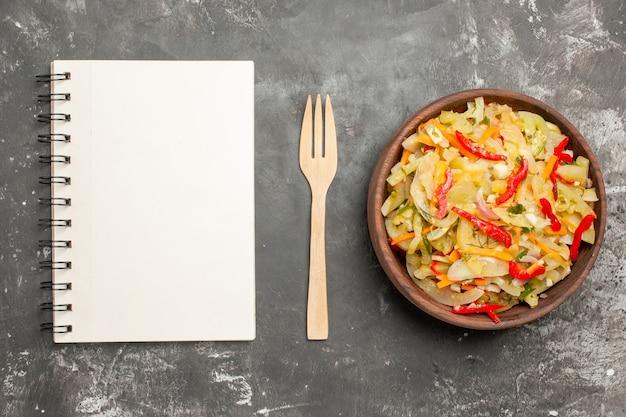 Insalata di vista ravvicinata superiore un'insalata di verdure appetitosa nel taccuino della forcella di legno della ciotola