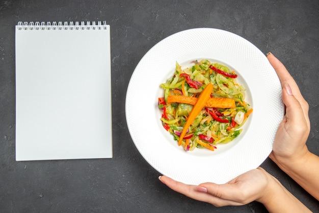 Верхний вид крупным планом салатная тарелка из аппетитного салата с овощами в руках белый блокнот