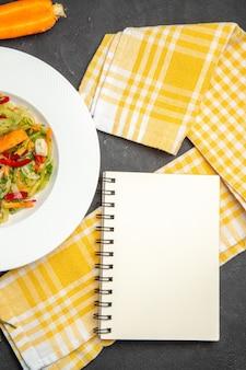 Top vista ravvicinata piatto di insalata di insalata con verdure tovaglia a scacchi notebook