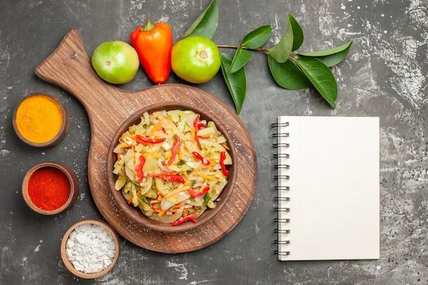 Верхний вид крупным планом салат, специи, болгарский перец с листьями, доска с миской салата, тетрадь