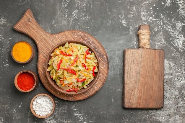 Top vista ravvicinata insalata di spezie insalata di verdure nella ciotola accanto al tagliere