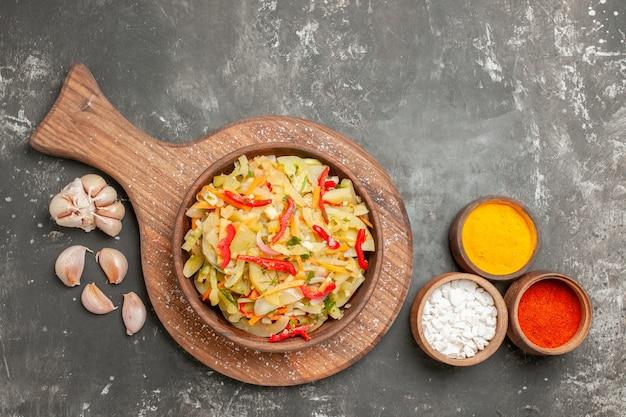 Top vista ravvicinata insalata di verdure insalata sul tagliere aglio e spezie