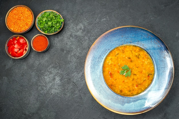 Сверху крупным планом суп тарелка супа с травами, травами, помидорами, специями, чечевицей