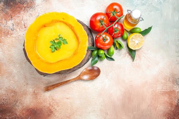 ボード上の上のクローズアップビュースープ柑橘系の果物スプーントマトオイルカボチャスープ