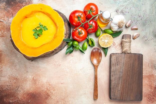 Top close-up view soup tomatoes garlic lemon oil pumpkin soup spoon the cutting board