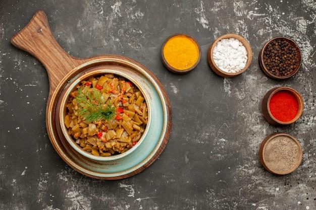 黒いテーブルの木製トレイにサヤインゲンとトマトの皿の横にあるさまざまなスパイスの上部のクローズアップビュースパイスと皿ボウル