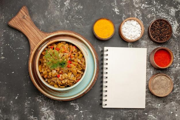 白いノートの横にあるさまざまなスパイスのスパイスと皿ボウル、黒いテーブルの木製トレイにあるサヤインゲンとトマトの皿の上部のクローズアップビュー