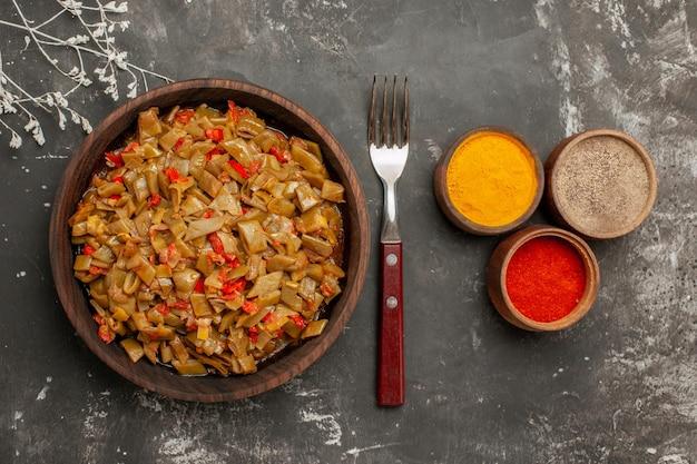 上部のクローズアップビュースパイスと皿暗いテーブルの上の緑の豆とトマトとフォークの木製プレートの横にあるカラフルなスパイスの3つのボウル