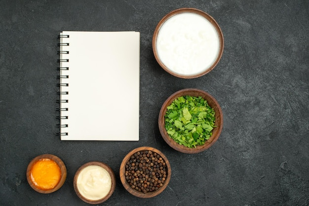 검은 표면에 있는 흰색 공책 옆에 있는 노란색 및 흰색 소스 허브 검은 후추와 사워 크림의 상위 클로즈업 보기 향신료와 소스 그릇