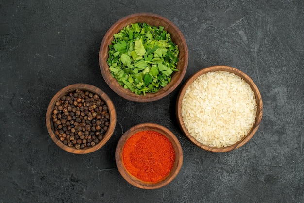 Top close-up view spices in bowls  colorful spices herbs and rice on the dark surface