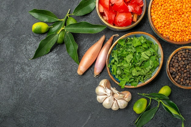 토마토 렌즈 콩 후추 허브 양파 마늘의 상위 클로즈업보기 향신료 그릇