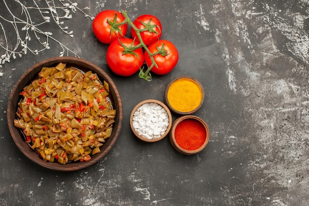 Vista ravvicinata dall'alto spezie ciotole di spezie e pomodori accanto al piatto di fagiolini e pomodori con pedicello sul tavolo scuro