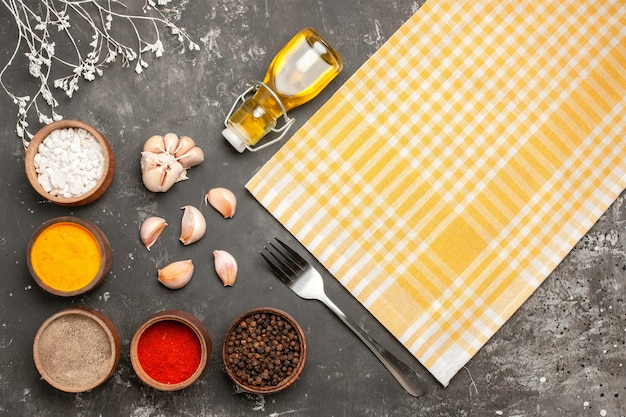 Top close-up view spices checkered tablecloth garlic bottle of oil spices fork