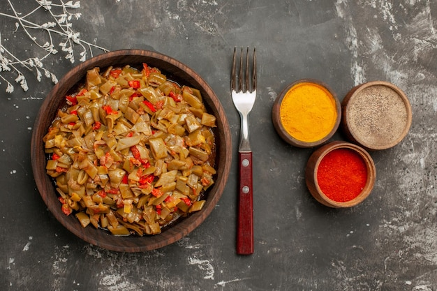 Spezie vista ravvicinata dall'alto e piatto tre ciotole di spezie colorate accanto al piatto di legno di fagiolini e pomodori e forchetta sul tavolo scuro