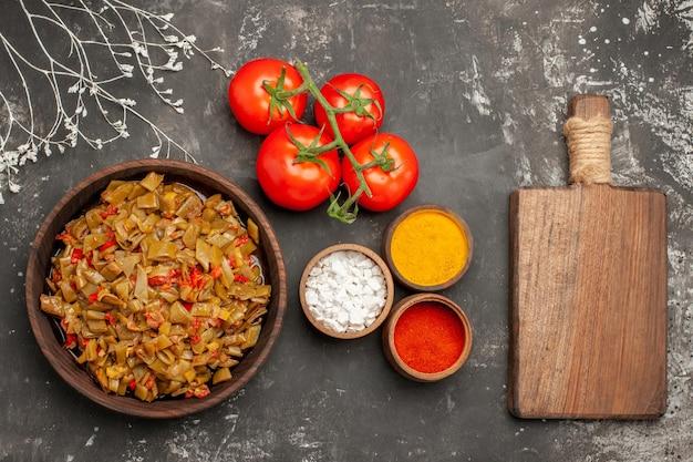Vista ravvicinata dall'alto spezie cinque ciotole di spezie colorate e pomodori accanto al piatto di fagiolini pomodori con pedicello e tagliere sul tavolo scuro