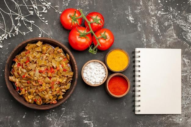 Vista ravvicinata dall'alto spezie cinque ciotole di spezie colorate e pomodori accanto al piatto di fagiolini pomodori con pedicello e quaderno bianco sul tavolo scuro
