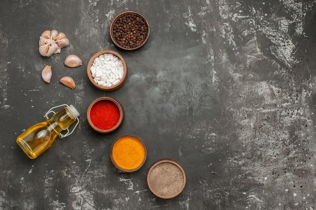 Top vista ravvicinata spezie cinque ciotole di spezie aglio bottiglia di olio sul tavolo scuro