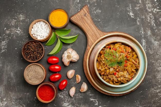 Vista ravvicinata dall'alto spezie fagiolini sul tagliere accanto alle ciotole di aglio di spezie colorate foglie pomodori con pedicelli bottiglia di olio sul tavolo scuro