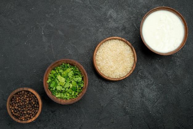 어두운 탁자 중앙에 있는 검은색 고추 허브 다채로운 향신료 쌀에 있는 상위 클로즈업 보기 향신료